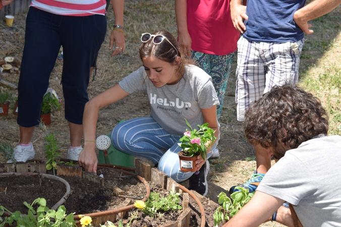 Voluntarios de Help Up trabajando en una espiral de plantas aromáticas.